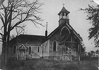 Wood-framed church with bell tower in the early 1900s