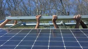 People lifting solar panels