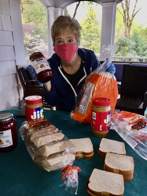 A parishioner in a mask and gloves holding a loaf of bread and a jar of jam. Sandwich making materials are spread out in front of her.