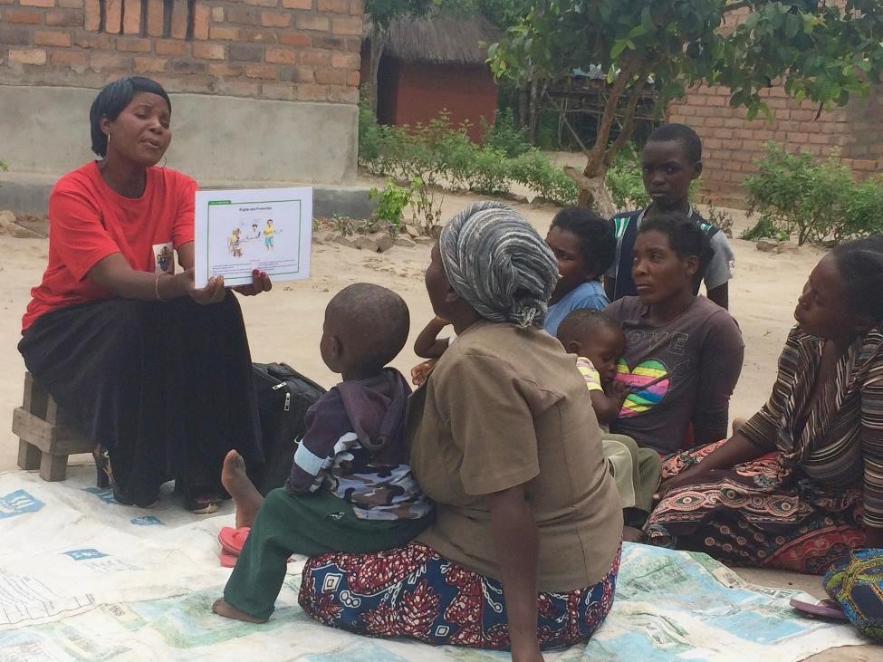 An African woman reads to a group of mothers and children