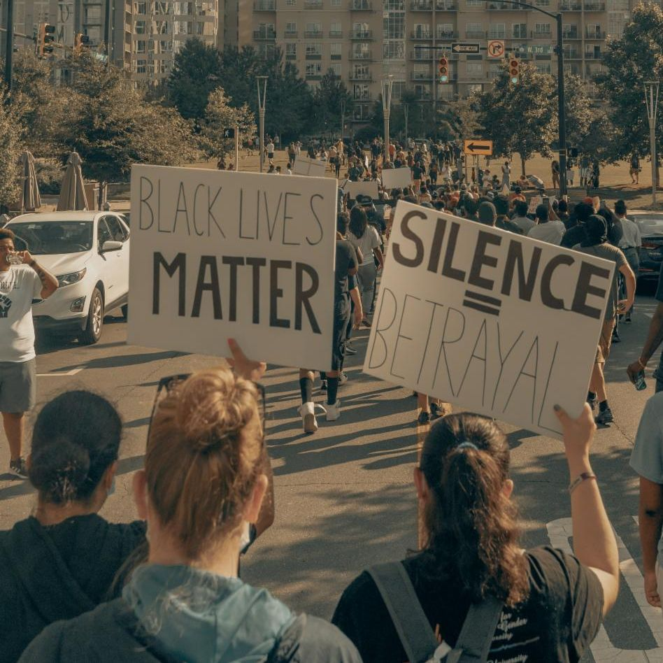 Protesters at a Black Lives Matter protest holding signs. First sign: Black Lives Matter. Second sign: Silence = Violence